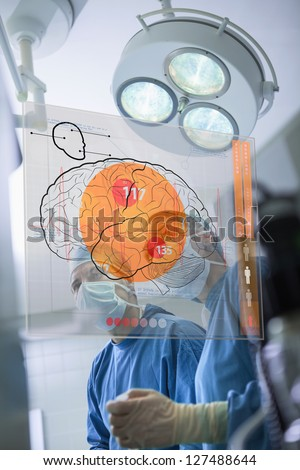 Two surgeons looking at the brain on an interface in surgery - stock photo