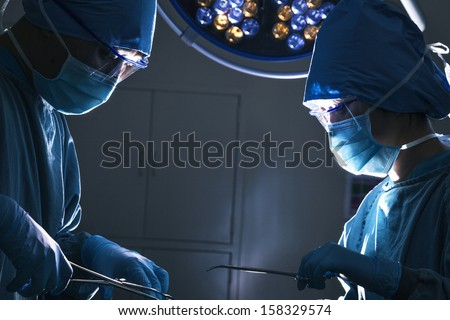 Two surgeons looking down and working at operating table - stock photo