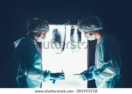 Two surgeons working and concentrating at operating table - stock photo