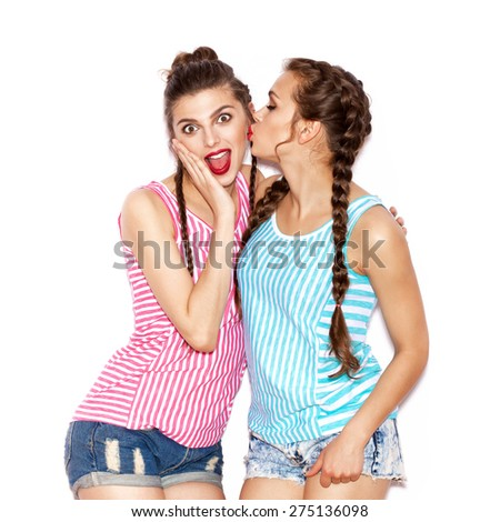 Two surprise painted  young women hugging and having fun. White background not isolated - stock photo