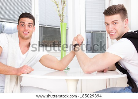 two surprised casual men arm wrestling - stock photo