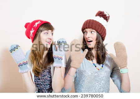 Two surprised funny young pretty women in winter knit cap and gloves looking at each other on white background - stock photo