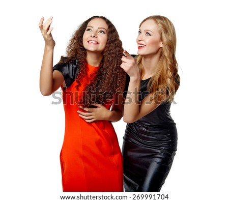 Two surprised girls friends with opened mouths pointing to blank copy space, isolated on white background - stock photo
