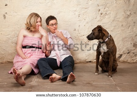 Two surprised ladies on the floor with pet dog - stock photo