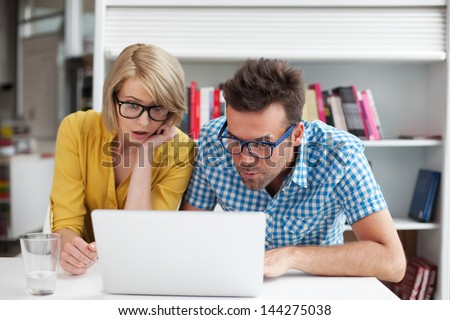 Two surprised students learning in library on laptop - stock photo
