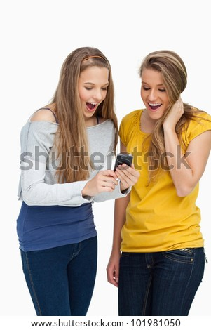 Two surprised students looking a cellphone screen against white background - stock photo