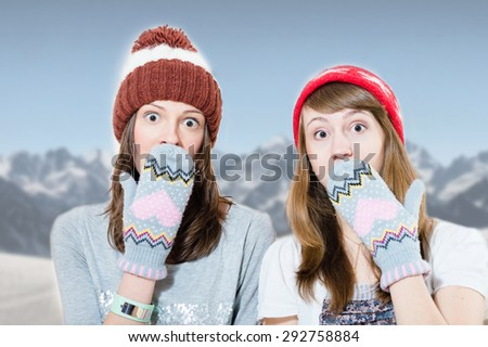 Two surprised young girls in hats and mittens covering mouth with hand on mountains background - stock photo