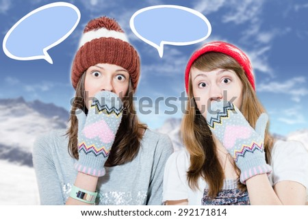 Two surprised young girls in hats and mittens covering mouth with hand on mountains background with speech bubbles - stock photo