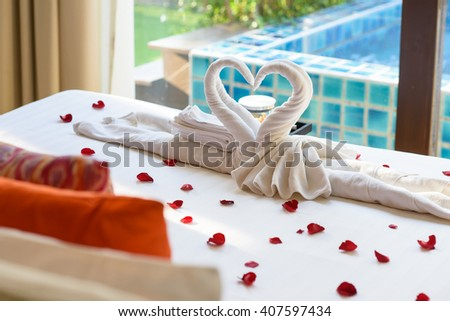 Two swans and heart made from towels on honeymoon bed - stock photo