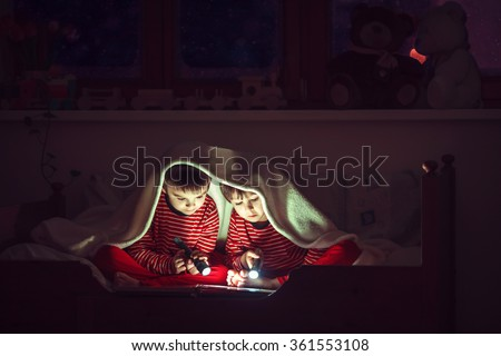 Two sweet boys, reading a book in bed after bedtime, using flashlights, winter night - stock photo