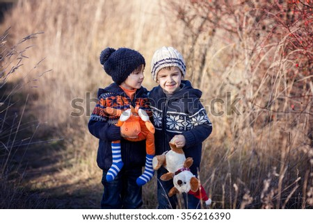 Two sweet boys with teddy bears, playing in the park on a sunny winter day, outdoors activity - stock photo