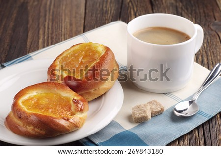 Two sweet buns with jam and cup of coffee on old wooden table - stock photo