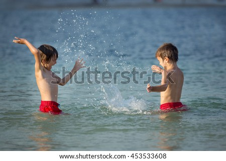 Two sweet children, boy brothers, splashing each other with water on the beach on sunset - stock photo