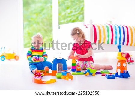 Two sweet children playing with toy cars, adorable curly toddler girl and a funny baby boy, brother and sister, sitting on the floor building blocks in a sunny white nursery with big window - stock photo