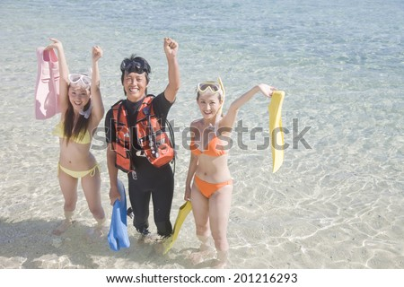 Two swimsuit women taking a commemorative photograph with a webbed foot in the water's edge and the man with a diving suit