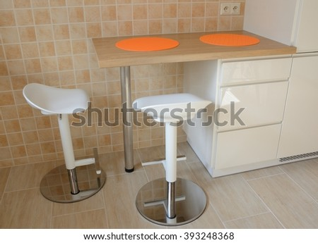 Two swivel stools and kitchen small table with orange rubber tablemats at wall covered with tiles - stock photo