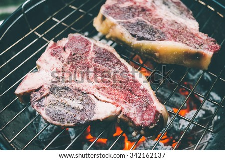 Two t-bone florentine beef steaks on the grill. Toned picture