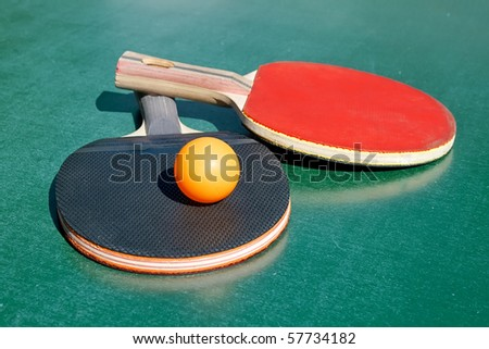 Two table tennis rackets and a ball on a green table - stock photo