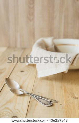 two tablespoons on a background of a linen cloth in the bowl, wooden interior