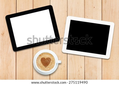 Two tablets and coffee on a wooden table