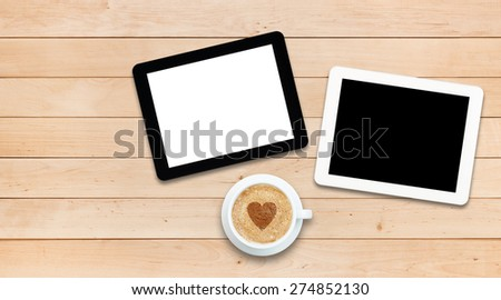 Two tablets PC and coffee on a wooden table