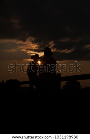 two  talking farmers sitting on a fence during sunset