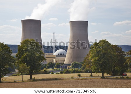 Two tall cooling towers and the reactor building of a nuclear power station in green river landscape seen from a hill.