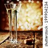 Two tall elegant flutes of romantic champagne on an old rustic wooden counter top against a sparkling bokeh of party lights celebrating a special occasion - stock photo