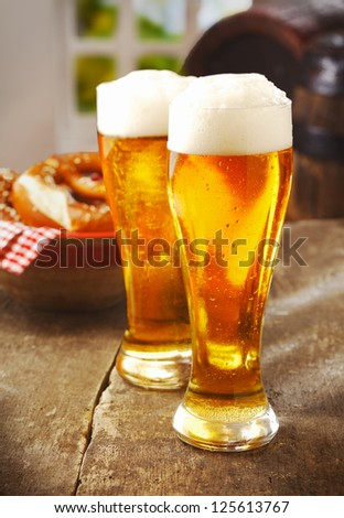 Two tall glasses of golden ale or beer with a good head of white froth on an old wooden kitchen table with a basket of rolls behind