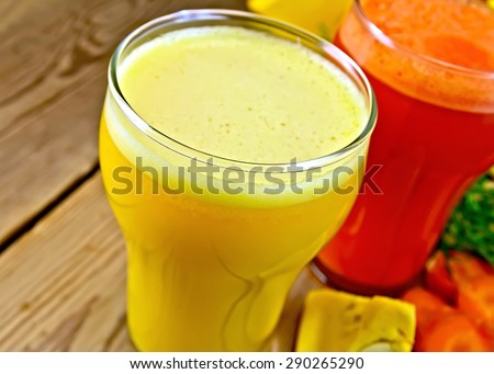 Two tall glasses of pumpkin and carrot juice, vegetables on a wooden boards background