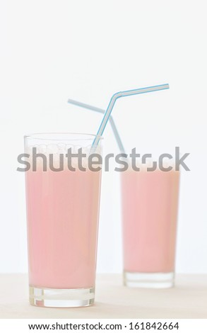 two tall glasses of strawberry milkshake with blue striped straws. - stock photo