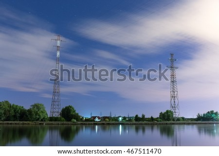 Two tall power line towers on the shore of the chanel at night