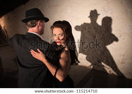 Two tango dancers performing under spotlight indoors - stock photo