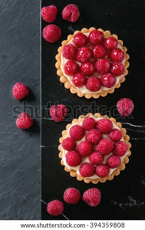 Two Tartlets with custard and fresh ripe raspberries, served on black marble board over stone slate surface. Top view - stock photo