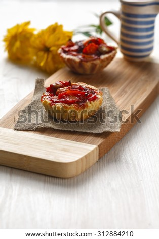 Two Tarts with apples on a cutting board decorated with textiles and ceramic creamer