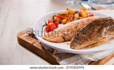 Two tasty grilled salmon trout fillets with copy space with vegetables on vintage plate for fish restaurants - stock photo