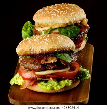 Two Tasty Hamburgers with Beef, Bacon, Lettuce, Tomatoes, Basil, Roasted Onion and Juicy Sauce on Sesame Buns on Wooden Cutting Board closeup on Dark Wooden background - stock photo