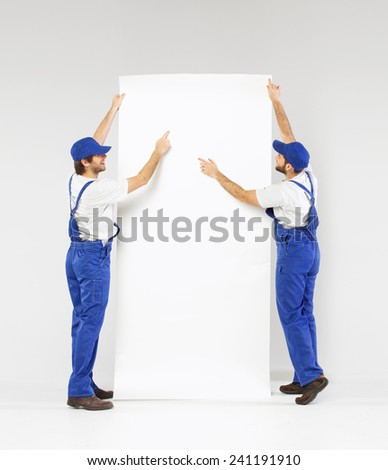 Two technicians holding a blank banner - stock photo