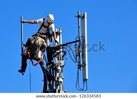 Two Technicians Working On A Telecommunication Tower