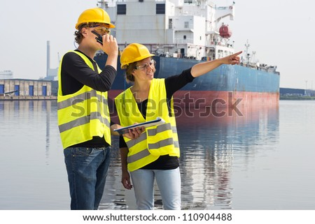 Two technology students discussing an assignment during an internship on site at an industrial harbor - stock photo