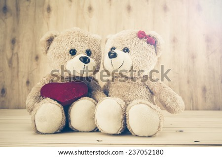 two teddy Bear with Heart on wood background,vintage tone,concept valentine - stock photo