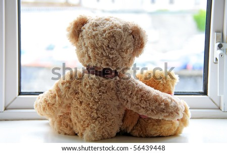Two teddy bears holding in one's arms - stock photo