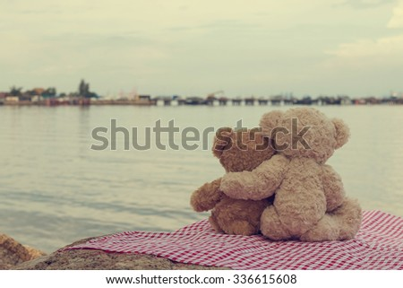Two teddy bears hugging. picnic sit on the fabric red and white looking the sea. vintage style. - stock photo