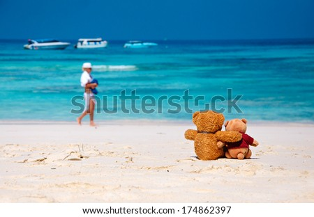 Two Teddy Bears sitting on the beach with blue sea and sky background. Concept about love friendship.