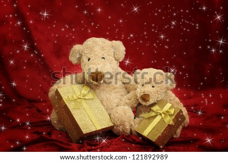 Two teddy bears with golden gift box on red stars background