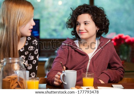 Two teen girl friends having breakfast together at home. - stock photo