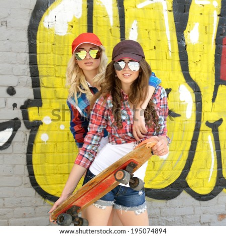 Two teen girl friends having fun together with skate board. Outdoors, urban lifestyle. - stock photo