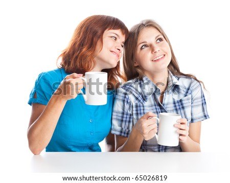 Two teen-girls are drinking tea. Isolated on white background - stock photo