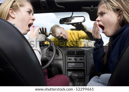 Two teen girls in a car with shocked and scared expressions on their faces after hitting a man while they were being distracted by eachother.