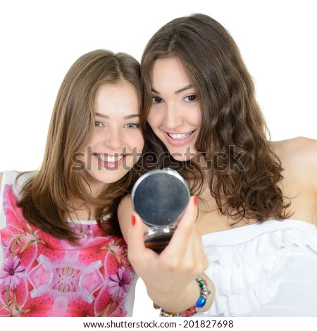 Two teen girls looking at herself in the mirror  - stock photo